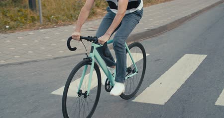 tracking : Young hipster young man in casual summer cloths riding his fixed gear bike along the bike lane on city street. Front tracking shot Side view Close-up of wheels. 4K slow motion raw video footage 60 fps