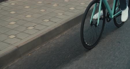 rögzített : Young hipster young man in casual summer cloths riding his fixed gear bike along the bike lane on city street. Front tracking shot Close-up of wheels. 4K slow motion raw video footage 60 fps