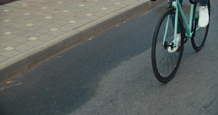 fix : Young hipster young man in casual summer cloths riding his fixed gear bike along the bike lane on city street. Front tracking shot Close-up of wheels. 4K slow motion raw video footage 60 fps