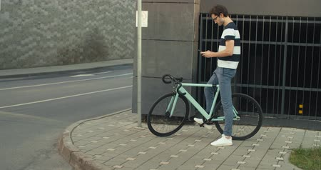 rögzített : people, style, technology, leisure and lifestyle - happy young hipster man with smartphone and fixed gear bike on city street 4K slow motion raw video footage 60 fps