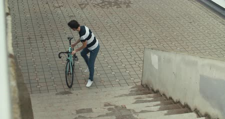 rögzített : Handsome man in carrying his bicycle while going up the stairs, 4K slow motion raw video footage 60 fps