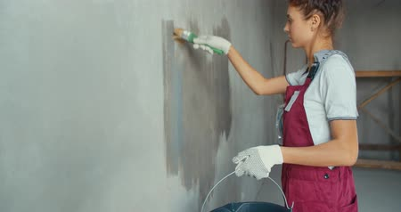 crépissage : One female house painter worker painting and priming wall with painting brush. Young woman in construction uniform. 4K slow motion raw video footage 60 fps Vidéos Libres De Droits