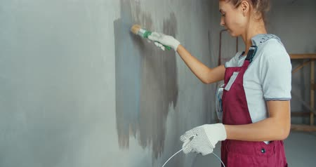 estuque : One female house painter worker painting and priming wall with painting brush. Young woman in construction uniform. 4K slow motion raw video footage 60 fps Vídeos