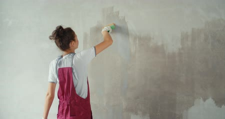 estuque : One female house painter worker painting and priming wall with painting brush. Young woman in construction uniform. Girl making repairs in the house. 4K slow motion raw video footage 60 fps