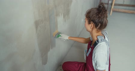 obnova : One female house painter worker painting and priming wall with painting brush. Young woman in construction uniform. Girl making repairs in the house. 4K slow motion raw video footage 60 fps