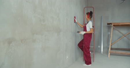 respirator : Repair and renovation at home. New interior design. Woman worker scrubbing wall with sandpaper and prepare surface for painting. Girl making repairs in house. 4K slow motion raw video footage 60 fps Stock Footage