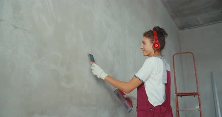 decorador : Repair and renovation at home. New interior design. Woman worker scrubbing wall with sandpaper and prepare surface for painting. Girl making repairs in house. 4K slow motion raw video footage 60 fps Stock Footage