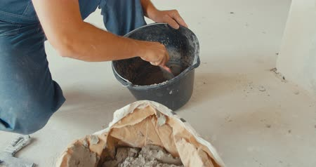 estuque : Construction bucket with dried mortar sluge on the concrete floor. Close up. Concept of repair and construction process. Finishing work at home. Rennovation and new interior. Woman hand putting used paper in recycled bin. Different color trash cans in row