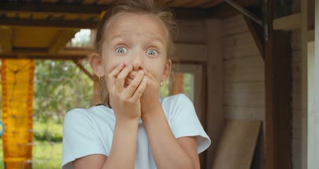 choque : Girl looks and is surprised and happy to receive a surprise. Portrait little young girl with blue eyes looking at camera. childhood, emotions concept. 4k raw slow motion footage video 60 fps