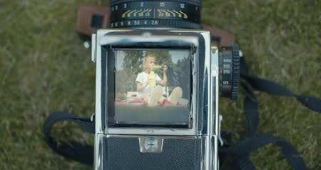 viewfinder : Shooting little girls portrait with old medium format camera. Cute kid blowing a soap bubbles in garden. Sunny day. 4k raw slow motion footage video 60 fps Stock Footage