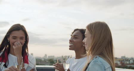 cena urbana : Outdoor shot of young people toasting drinks at rooftop party. Young girl friends hanging out with drinks, talking, chatting , celebrating birthday. 4k slow motion raw video footage 60 fps