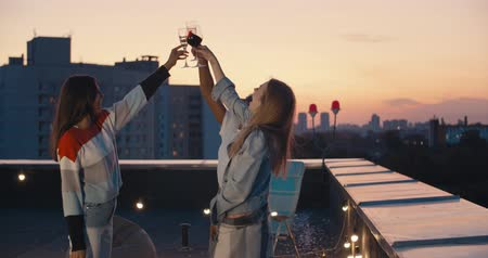 bílé víno : Outdoor shot of young people toasting drinks at rooftop sunset party. Young girl friends hanging out with drinks, talking, chatting , celebrating birthday. 4k slow motion raw video footage 60 fps Dostupné videozáznamy