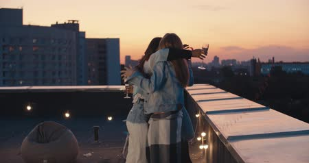 white wine : Outdoor shot of young people toasting drinks at rooftop sunset party. Young girl friends hanging out with drinks, talking, chatting , celebrating birthday. 4k slow motion raw video footage 60 fps Stock Footage
