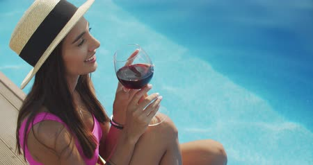 adega : Smiling woman sitting on the pool edge with glass of wine. Beautiful woman relaxing outdoors at summer sunny day. 4k raw slow motion video footage