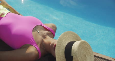 à beira da piscina : Resting girl or woman relaxing near swimming pool, enjoying her time, holding and moving her hand in water, wearing swimsuit summer clothing. 4k raw slow motion video footage