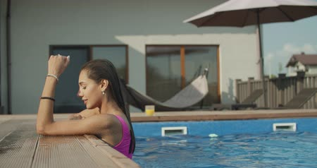mayo : Beautiful young woman smiling in a swimming pool, under the golden summer light. 4k raw slow motion video footage Stok Video