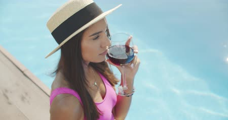 bílé víno : Smiling woman sitting on the pool edge with glass of wine. Beautiful woman relaxing outdoors at summer sunny day. 4k raw slow motion video footage