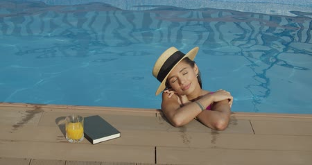 nyaraló : Close-up of relaxing woman in hat bathing and chilling in infinity pool in luxury spa resort villa. 4k raw slow motion video footage