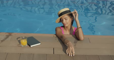 à beira da piscina : Close-up of relaxing woman in hat bathing and chilling in infinity pool in luxury spa resort villa. 4k raw slow motion video footage