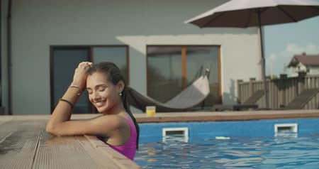 дубленый : Beautiful young woman smiling in a swimming pool, under the golden summer light. 4k raw slow motion video footage Стоковые видеозаписи