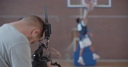 camera operator : Videographer taking video shots of basketball afro-american man on training in gym. Black guy making slam dunk during game in court. Player wearing unbranded sport clothes. Slow motion 4k raw 60 fps Stock Footage