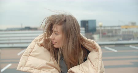 Close-up portrait of young attractive europian woman wearing coat looking at camera at rooftop of parking at city center feel happy fashion girl face