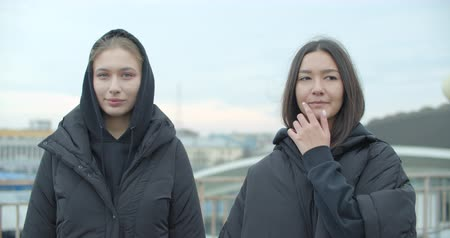 Two young attractive women wearing black coat with hood looking at camera at rooftop of parking at city center feel happy fashion girls faces. 4k raw video slow motion 60 fps