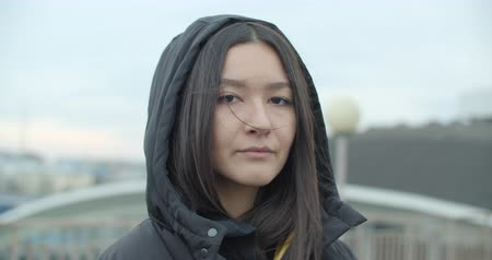 Close-up portrait of young attractive arabian woman wearing black coat with hood looking at camera at rooftop of parking at city center feel happy fashion girl face. 4k raw video slow motion 60 fps Dostupné videozáznamy