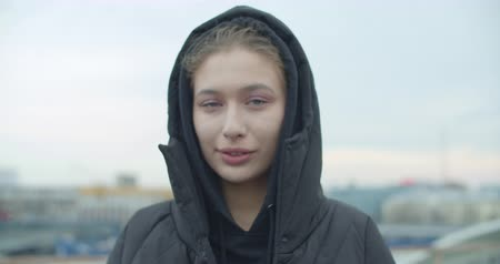 Close-up portrait of young attractive europian woman wearing black coat with hood looking at camera at rooftop of parking at city center feel happy fashion girl face. 4k raw video slow motion 60 fps Dostupné videozáznamy
