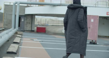 Young attractive caucasian woman wearing black coat with hood walking at rooftop of parking at city center. Pretty naughty fashion girl Stockvideo