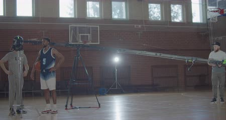 film camera : A professional videographer taking video shots of basketball afro-american man on training in gym. Black guy with ball playing on playground. Slow motion 4k raw footage 60 fps Stock Footage