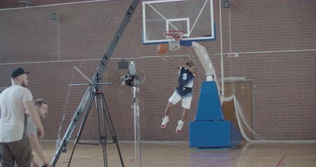 Videographer taking video shots of basketball afro-american man on training in gym. Black guy making slam dunk during game in court. Player wearing unbranded sport clothes. Slow motion 4k raw 60 fps Dostupné videozáznamy