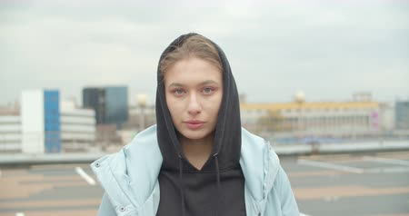 Close-up portrait of young attractive europian woman wearing blue coat and black hoodie looking at camera at rooftop of parking at city center feel happy fashion girl face Dostupné videozáznamy