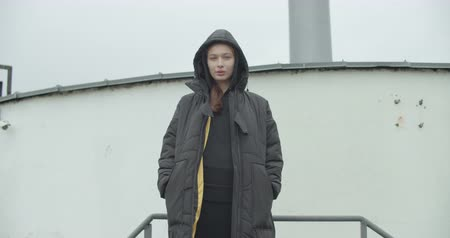Young attractive caucasian woman wearing black coat with hood looking at camera at rooftop of parking at city center feel happy fashion girl face