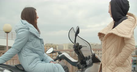Side view of two attractive woman in coat sitting on motorbike . Friends talking Filmati Stock