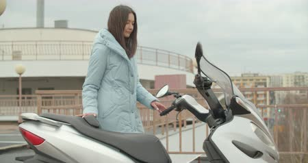 Side view of attractive arabian woman in blue coat sits down on modern motorbike. Trendy casual autumn spring outfit. Urban fashion Dostupné videozáznamy
