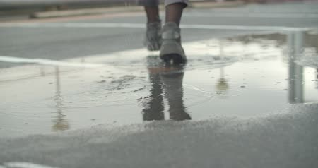 yağmur yağıyor : Close up shot of womens legs stepping into puddle and making splash Stok Video