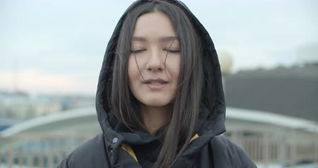 Close-up portrait of young attractive arabian woman wearing black coat with hood looking at camera at rooftop of parking at city center feel happy fashion girl face 4k raw video slow motion 60 fps