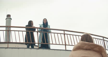 Young attractive women wearing black coat with hood standing at rooftop of parking at city center. Pretty naughty arabian and caucasian fashion girls friends . 4k raw video slow motion 60 fps