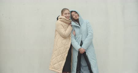 Two young smiling hipster women in autumn clothes. Girls posing in street near wall. Female having fun Dostupné videozáznamy