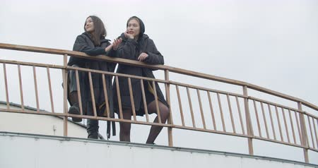 Two young attractive women wearing black coat with hood standing at rooftop of parking at city center. Pretty naughty arabian and caucasian fashion girls friends