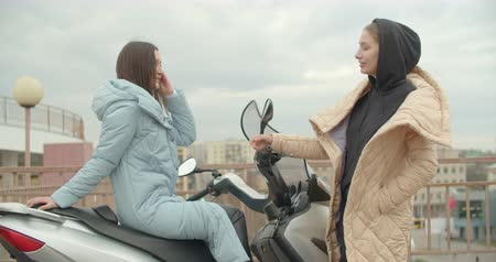 Side view of two attractive woman in coat sitting on motorbike . Friends talking Dostupné videozáznamy