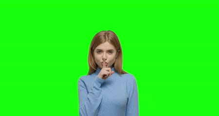 конфиденциальный : Young woman showing silence sign. Blonde girl putting finger on mouth in green screen studio. Beautiful female keeping secret holding finger on lips. Chroma Key. 4k video footage slow motion 60 fps Стоковые видеозаписи
