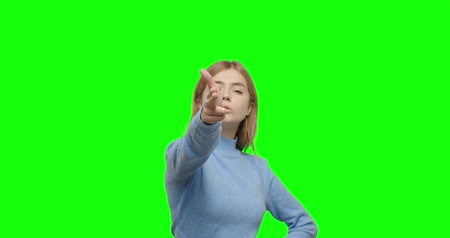 пистолеты : Young woman shooting gesture on green screen Close-up of girl making sign gun by hand posing at green screen studio background. Chroma Key 4k video footage slow motion 60 fps Стоковые видеозаписи