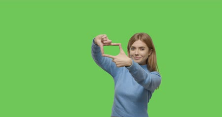 encadrement : Cheerful young woman making frame with hands. Portrait of female winking while looking through imaginary camera made with fingers on Green Screen, Chroma Key. 4k video footage slow motion 60 fps