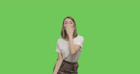 air kiss : Flirtatious young playful beauty blowing and sending air kisses to camera. Half body over green screen background. Chroma Key 4k raw video footage slow motion 60 fps Stock Footage