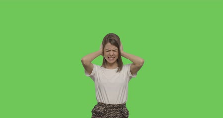 grimacing : Girl closes her ears with her hands isolated on Green Screen, Chroma Key. 4k raw video footage slow motion 60 fps
