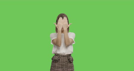 shy girl : Shy girl smiling. Young pretty woman close her face by hands on green screen background, Chroma Key 4k video footage slow motion 60 fps