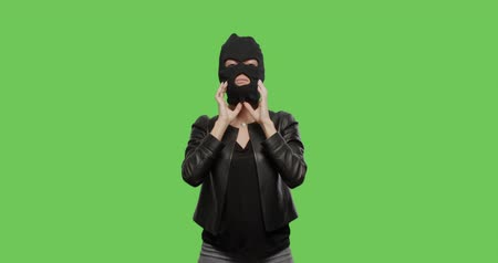 bandido : sexy woman take on burgal mask- crime and violence on green background . Naughty girl in burgal mask having fun . Chroma Key. 4k raw video footage slow motion 60 fps