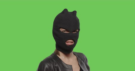 haydut : Close-up of woman in balaclava - crime and violence on green background . Naughty girl in burgal mask having fun . Chroma Key. 4k raw video footage slow motion 60 fps